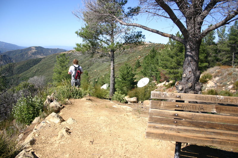 Approach to Cathedral Peak starts near the bench and heads West toward a pair of satellite dishes.  Follow a cleared trail down a ridge to the saddle between La Cumbre Peak and Cathedral Peak.