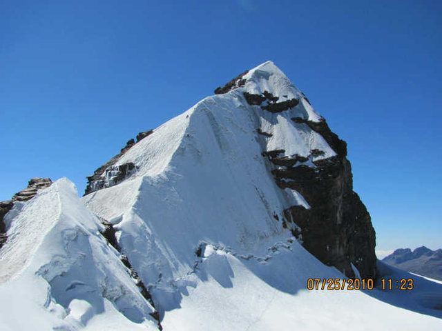 Pequeno Alpamayo in Bolivia, the Standard Route heads up the ridge on the left skyline and the Direct Route heads up the center along the corner before crossing right under the rocks and then up to the summit