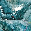 """Finishing a mellow pitch on the Rock Rib.  Directly behind the climber is the """"Upper Snowfield"""", and to the upper left, the Snow Ledge is visible."""