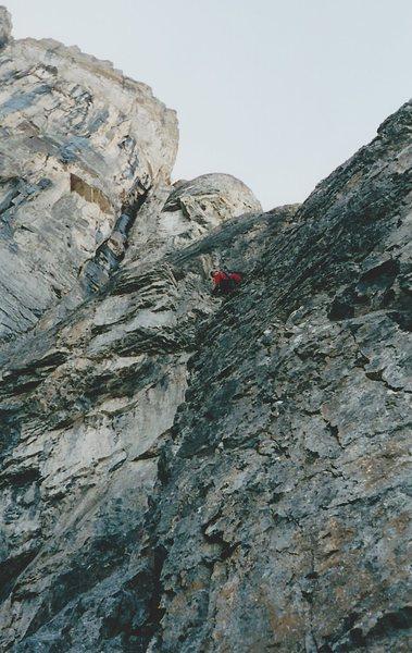 Climbing the cruxy slab near the top of the Rock Rib.