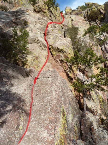 The route starts in the shallow dihedral left of center. It then follows the jagged crack in the flake above before a hand traverse right to another crack.  The crux is the open book below the small tree at the top, center of the photo.