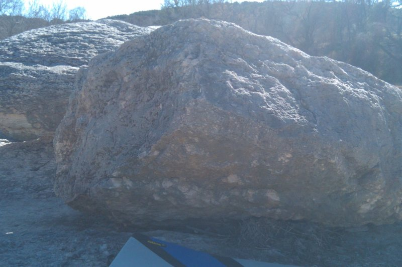 The problem starts around the left hand side of the boulder pictured. Keep your feet under the overhang as you traverse through.