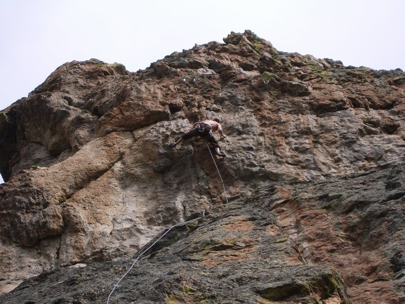Nick Duttle climbing through the upper headwall to the chains on High Tide.