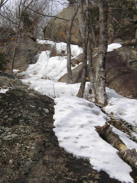 A January thaw reveals the line of <em>Isobuttress Left</em>, winding up along side of the main cliff.