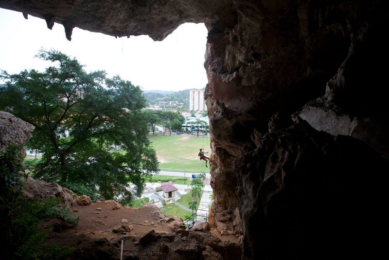 Anja lowering from the first 30 m of Dry Season.  Looking out from the cave.  Photo by Ram Sripracha.
