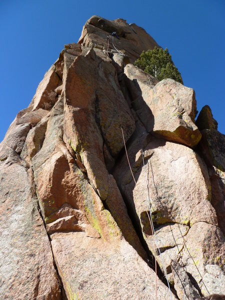 The route with a climber just below and to the left of the crux roof moves.