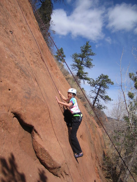 Jackie Paik solving the crux move.  (Camera angle makes rock appear steeper than actual slope@SEMICOLON@ note trees.)