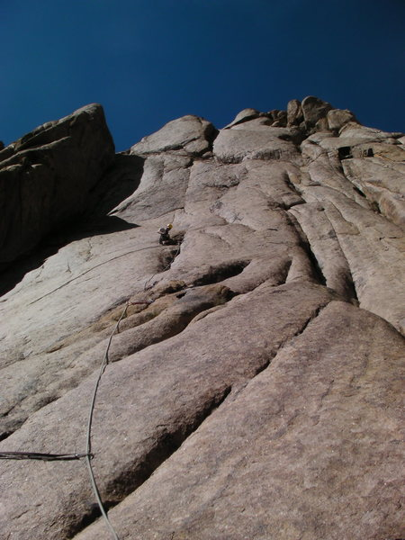 This pic is on the second pitch of the FA.  The line goes straight up to the small shadowed dihedral above and slightly to the right of me.  The first two pitches are 5.6-7.  Third is an awkward 5.9 zig zag to a belay under the roof at the base of the dihedral.  Don't forget you are at nearly 12,000 feet and will get tired fast if you haven't aclimatized.
