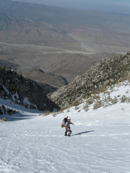 Paul cruising up the snow chute.  The starting elevation can be seen wayyyyy in the background
