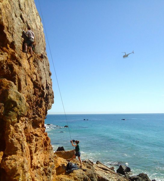 Typical occurrence at this crag: Random helicopters flying by all the time, dolphins swimming offshore, and cute girls doing bikini photo shoots in the rocks at the base. A great day at the beach if you don't mind washing ALL your gear afterward...