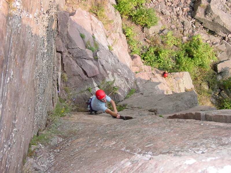 Mark Bratlie on the ledge between the 5.6 lower section & the 5.9 crack w/ Laura Machacek belaying.<br> Photo by: Matt Johnson