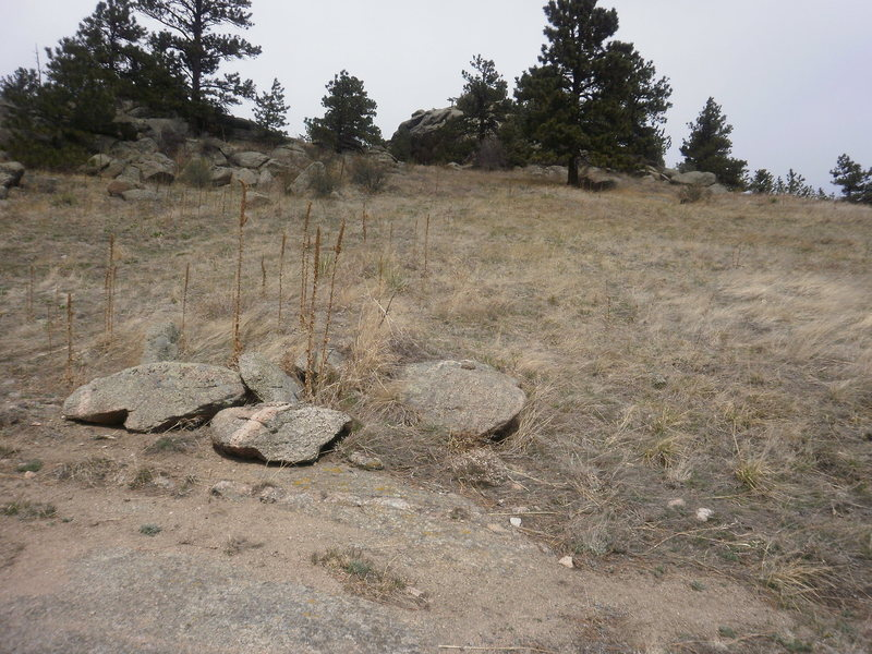Looking west @ the boulder from the approach road.  These rocks mark the cut off....