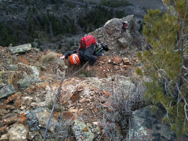 Topping out the direct finish on the 4th pitch by pulling on some grass. Canyon Cruiser, Glenwood Canyon.