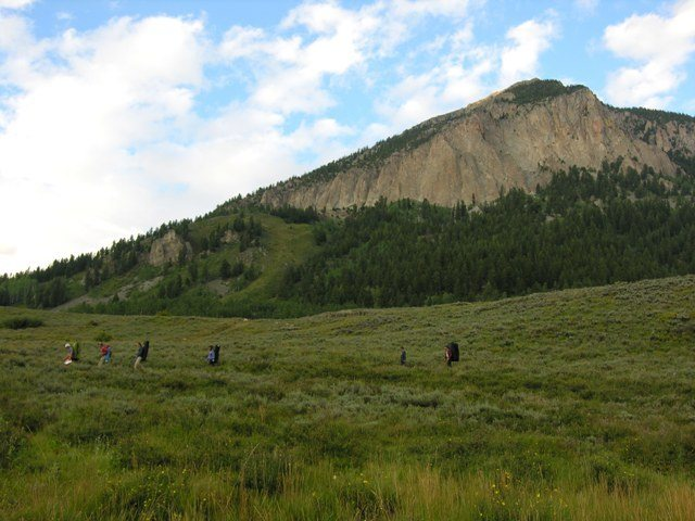 Climbers hiking down Tony's Trail, with Mt. Crested Butte in the background.