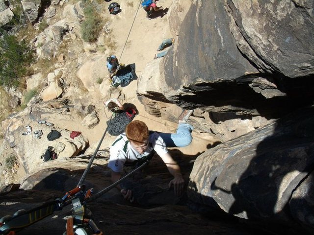 View from the top.  Eric about to top the route, with view of belaying area underneath him.