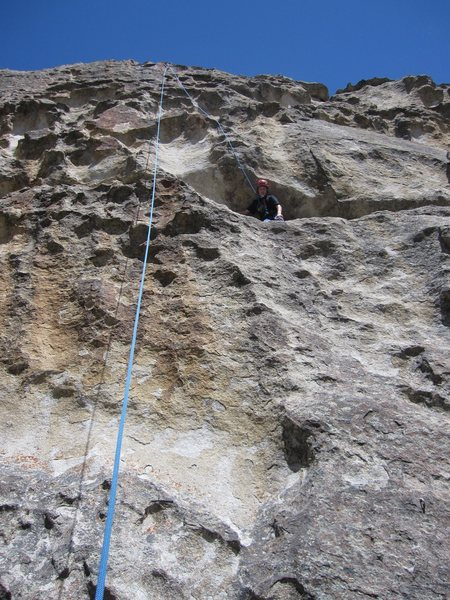 Noah standing in the ledge before the crux moves up in the white blank area up/left.