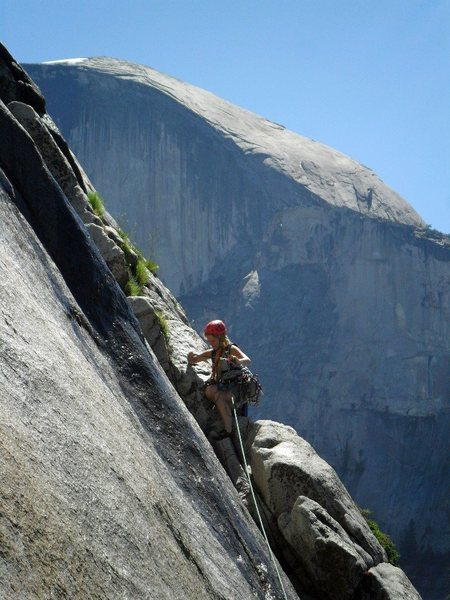 Brenda cleaning the belay station just above the fixed pendulum.  Note the water on the rock in the foreground -- it was pretty wet up there, and Half Dome in the background.