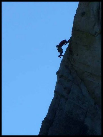 Unknown climber clearing the classic arete on the third pitch.