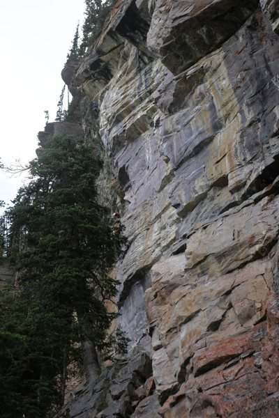 A climber completing the arete taken by the upper pitch of Venom, 5.11d