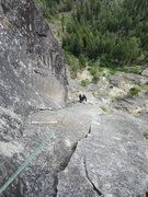 Looking down from belay 2 at the delightful 5.9 finger crack system that begins after a leftward traverse.  You can also see the scramble gully (p0 in the route description) in the background.