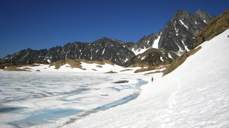 A frozen Ingalls Lake with Mt. Stuart in the background