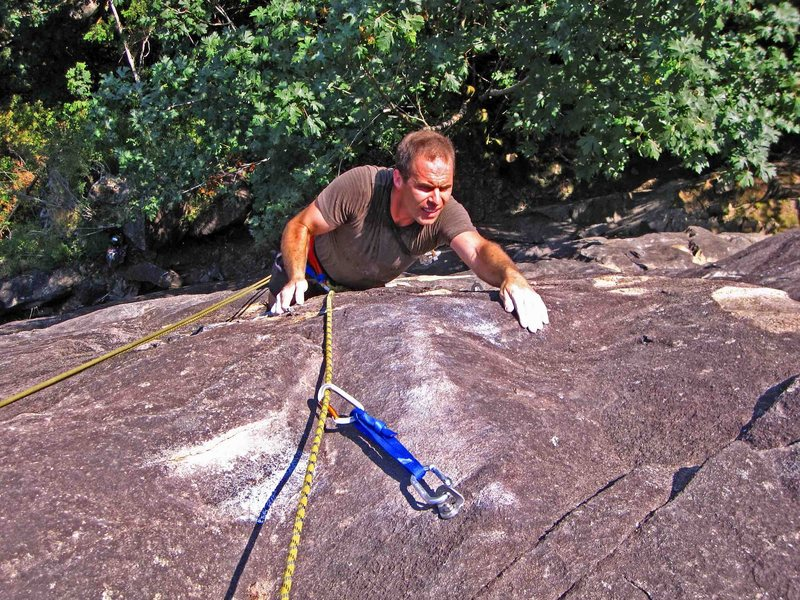 Derek Pearson doing the pumpy crux over the top bulge. (Just after unclipping a bolt.)