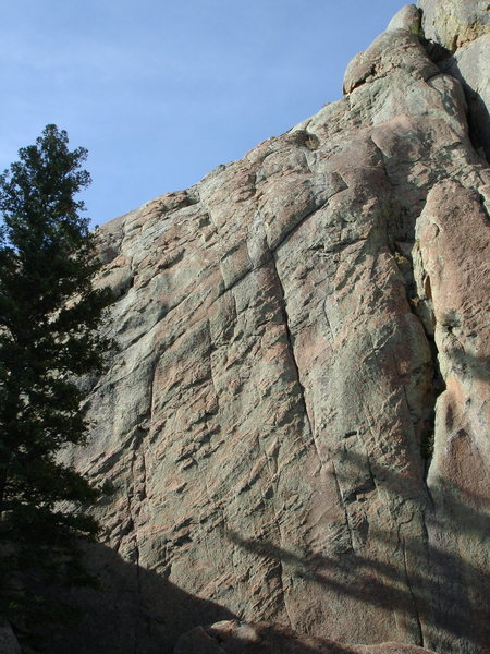This route starts in the shade at the lower left and moves up and right past thin cracks until the 3rd one where you move up and slightly left onto the face at a small roof/tips crack. Continue up to a broken ledge to belay.