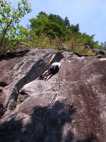 Climber at the crux of Tilt, 5.11b/c.