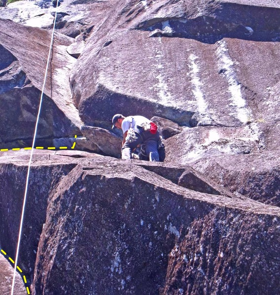 Derek on pitch 5. He is at the 10b crux of the lower ramp/corner. The bottom of the steeper corner just above has the crux. <br> <br> Yellow dashed line shows a variation start to the pitch. Much harder than the way Derek is on.