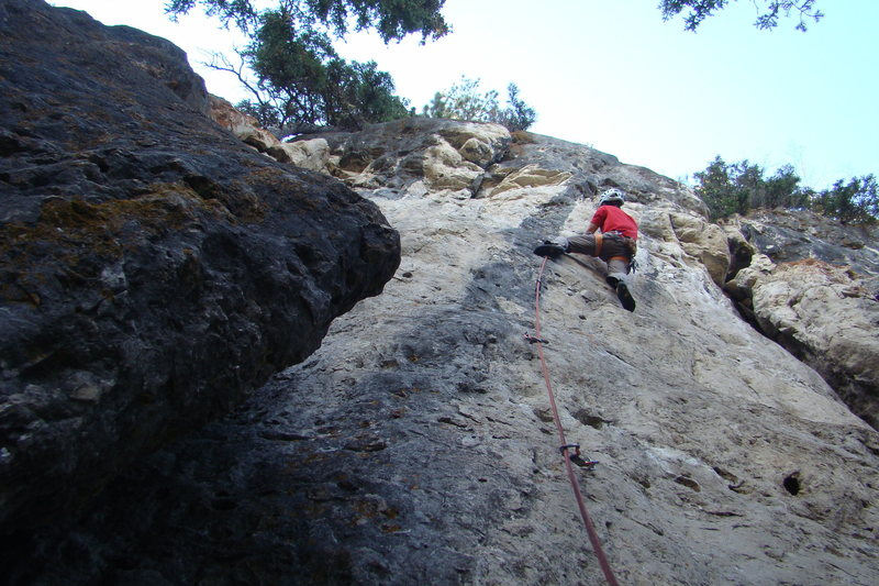 A climber in a red shirt on Black Rainbow.