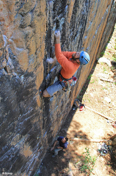 Alex on better holds just past the slopey crux during FA - The Yardstik (5.11+).