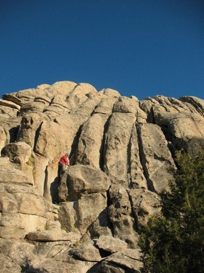 Starting Pluton Playground@SEMICOLON@ route follows dark chimney-crack above climber's head.