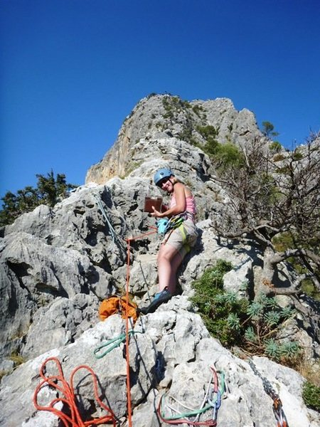 LeAnn signing in the route book at the top of Albahida.  <br> <br> Finish ridge scramble in the background.