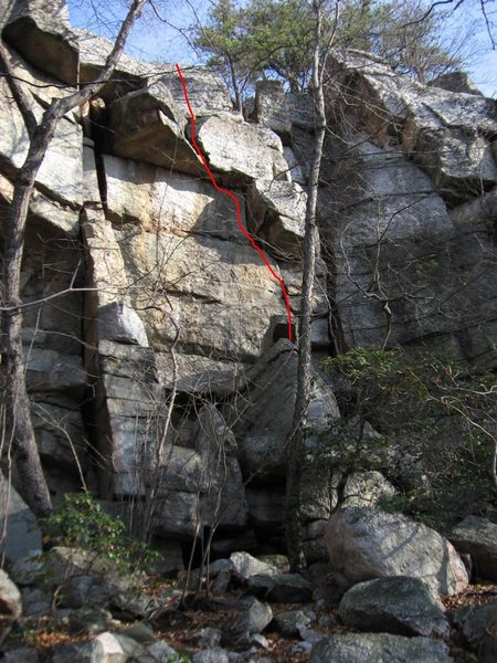 "Core Shot (line).  Also visible is ""Shotty Not"", the squeeze offwidth that starts at the right side of the boulder pile and ends at the pine tree (5.5 or 5.6)."