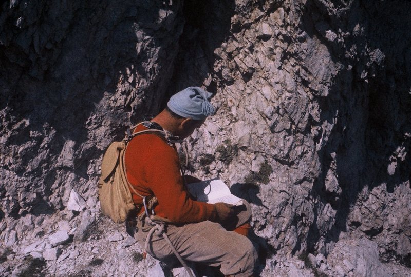 """""""Toto"""" signing the route register, which is on a ledge one pitch below the summit."""