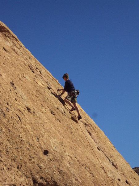 "A climber above the crux of ""Aenea."""