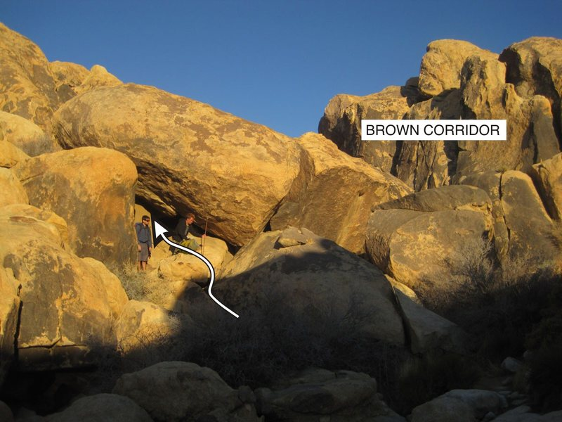 If you go to this cave entrance on the south end of the corridor you can scoot up an easy slab then head right through a tunnel, boulder hop and you're right under Mojave Green Arete.