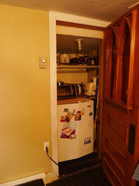 refrigerator (behind salvaged church door)