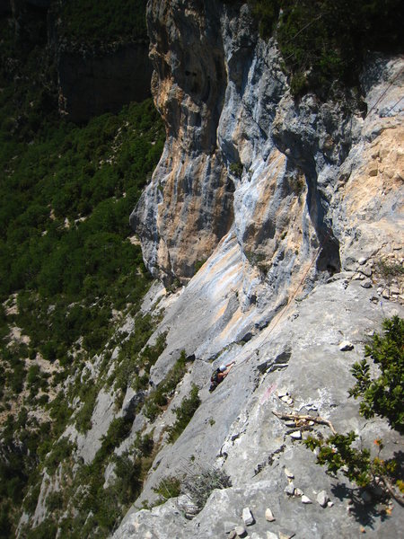 Looking down on the last 2 pitches.  The final roofs are hidden in shadows above the climber.  Down and to the left of the climber, the 4th pitch follows the arcing line of pockets that straddle the line between the streaked rock and the gray face.