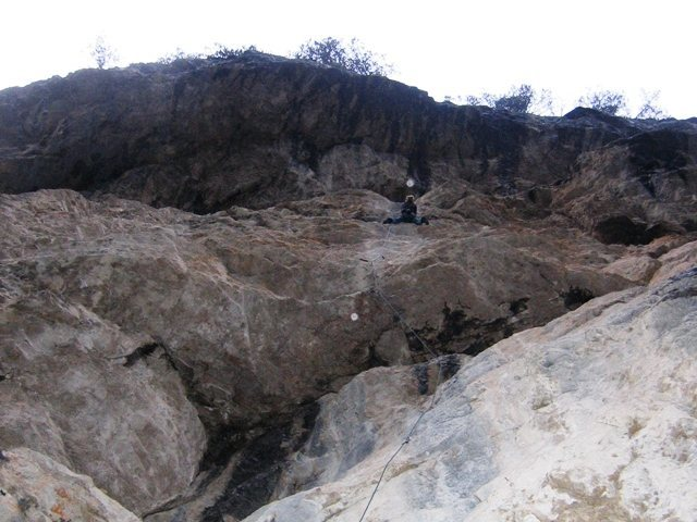 Steep rock under overhangs:  climbing in the rain at Landro