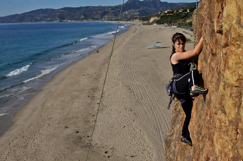 Sara climbs a route on the seaside on a beautiful day.