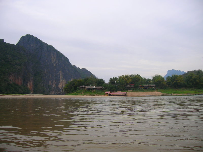 The impressive wall to the left and the small village of Pak Ou from the waters of the Mekong on a slowboat ride.