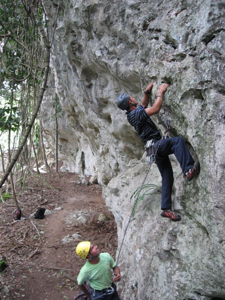 Belizean adventure guides Dennis Martinez & Justo Navas climbing Jungle Fun (5.5), a four bolt route in the Cayo District of Belize.