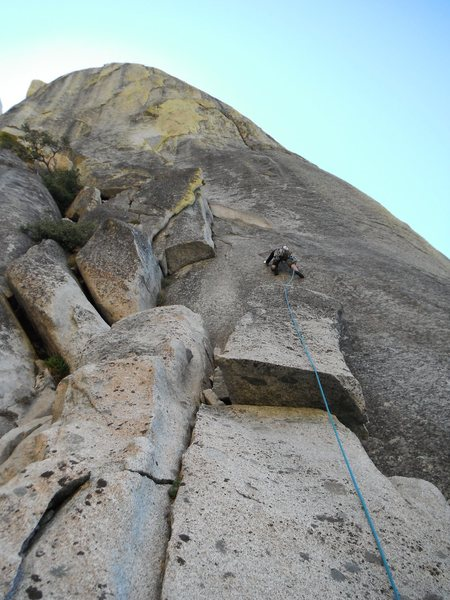 Rob Beno leading P1 of Silver Threads. The left-leaning corner 20&@POUND@39@SEMICOLON@ above the climber is dirty and vegetated. The attractive yellow flakes of P2 & P3 can be seen above.