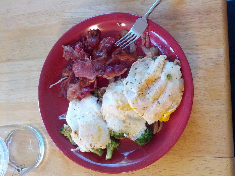 3 over-easy eggs on top of broccoli, onions, mushrooms sauteed in bacon fat, with the bacon on the side.