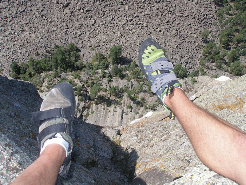 Looking down from the West side of Devils Tower. We are clipped into two rappel bolts.
