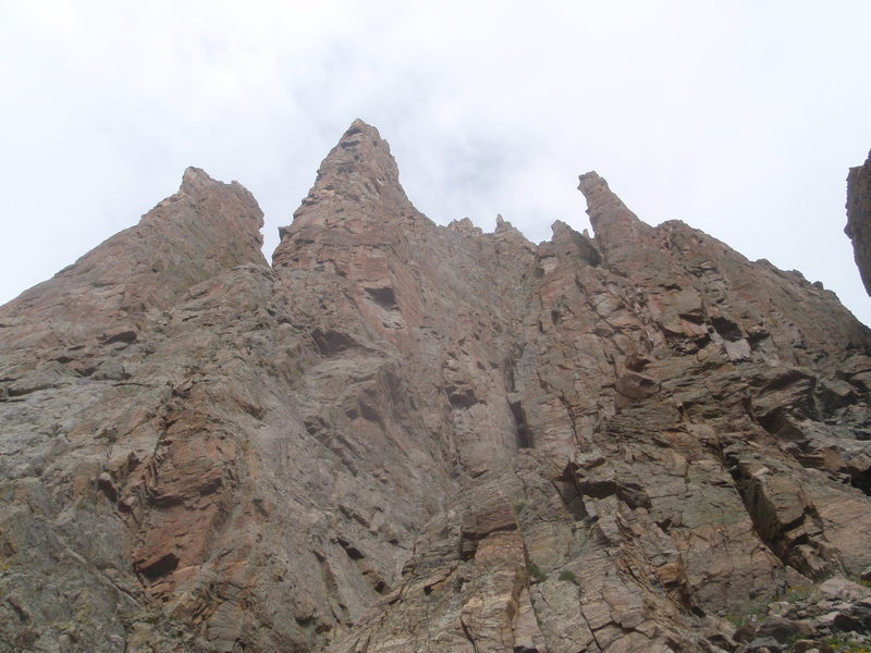 From left to right (west to east) The Petit Grepon, The Saber, The Foil. The South Face of the Foil starts at a grassy ledge below a steep loose corner about 100 feet above you.