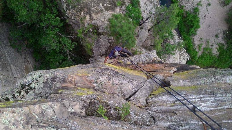 Arjun cleaning on rap. Drops into the ledge below. The route goes to my left down a slope to the chimney. Rap the tree.