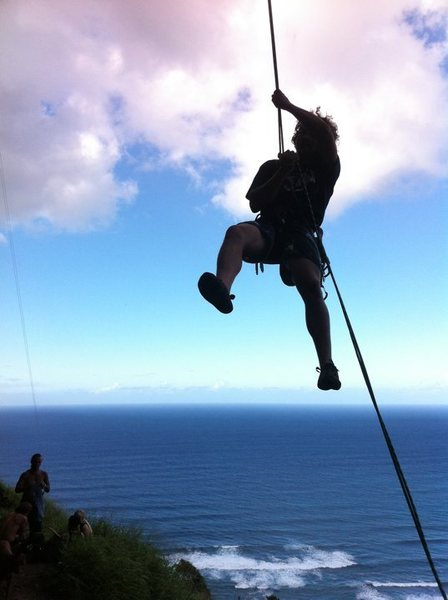 Travis rappelling off a route at the Mokuleia Wall, Hawaii