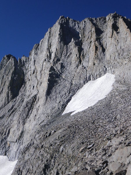 21-August-2012: We approached by heading across the talus below the snowfield, then up some fourth class (partially in shade here) to the start of the dihedral.